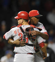 Cincinnati Reds' Devin Mesoraco left, hugs Aroldis Chapman after the Reds defeated the Chicago Cubs 6-4 in eleven innings after a baseball game Tuesday, Aug. 13, 2013, in Chicago. (AP Photo/Jim Prisching)