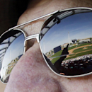 Jerome Oppenheim, of Sun City, Ariz., points to the main stadium field, shadow reflected in glasses, at the Peoria Sports Complex as he talks with friends while watching the Cleveland Indians and Seattle Mariners in the sixth inning of a spring training b