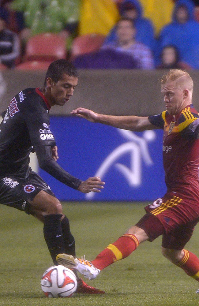 Club Tijuana's defender Javier Salas, second from left,  is beaten to the ball by Real Salt Lake midfielder Luke Mulholland, second from right, Tuesday, Aug.12, 2014, at Rio Tinto Stadium in Sandy, Utah