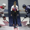 Olympic women's hockey player Jocelyne Larocque drops the puck between Phoenix Coyotes' Oliver Ekman-Larsson (23) and Winnipeg Jets' Olli Jokinen (12) prior to NHL hockey game action in Winnipeg, Manitoba, Thursday, Feb. 27, 2014. (AP Phoyo/The Canadian P