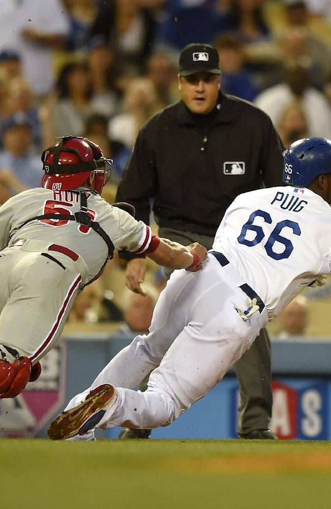 Los Angeles Dodgers' Yasiel Puig, right, is tagged out by Philadelphia Phillies catcher Carlos Ruiz after being caught between third and home on a single by Adrian Gonzalez during the first inning of a baseball game, Monday, April 21, 2014, in Los Angeles