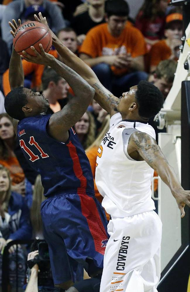 Oklahoma State wing Le'Bryan Nash (2) blocks a shot by Robert Morris forward Jeremiah Worthem (11) in the second half of an NCAA college basketball game in Stillwater, Okla., Monday, Dec. 30, 2013. Oklahoma State won 92-66