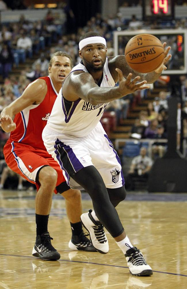 Sacramento Kings center DeMarcus Cousins, right, goes after the ball as Los Angeles Clippers  forward Lou Amundson, left, looks on during the third quarter of an NBA preseason basketball game in Sacramento, Calif., Monday, Oct. 14, 2013.   The Kings won 99-88