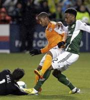 Houston Dynamo defender Corey Ashe, middle, holds off Portland Timbers forward Rodney Wallace, right, as Houston goalie Tally Hall makes a diving save during the second half of an MLS soccer game in Portland, Ore., Saturday, April 6, 2013.  Portland won 2-0.(AP Photo/Don Ryan)