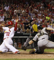 St. Louis Cardinals' Jon Jay (left) scores the game-winning run past Pittsburgh Pirates catcher Russell Martin on a single by Adron Chambers in the 14th inning during a game between the St. Louis Cardinals and the Pittsburgh Pirates early Wednesday, Aug. 14, 2013, at Busch Stadium in St. Louis. (AP Photo/Post Dispatch, Chris Lee)