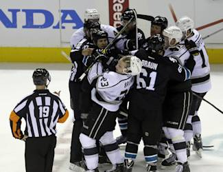 Referee Gord Dwyer (19) watches a fight between the San Jose Sharks and the Los Angeles Kings during the third period of Game 2 of an NHL hockey first-round playoff series Sunday, April 20, 2014, in San Jose, Calif. (AP Photo/Ben Margot)