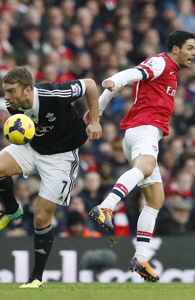 Arsenal's Mikel Arteta, right, competes for the ball with Southampton's Rickie Lambert during the English Premier League soccer match between Arsenal and Southampton at the Emirates Stadium in London, Saturday, Nov. 23, 2013
