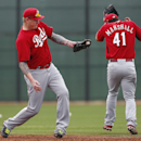 Cincinnati Reds pitcher Mat Latos fields a ground ball as Brett Marshall covers up during spring training baseball practice in Goodyear, Ariz., Tuesday, Feb. 25, 2014 The Associated Press