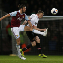 West Ham United's Andy Carroll, left, competes with Manchester United's Phil Jones during their English Premier League soccer match at Upton Park, London, Saturday, March 22, 2014