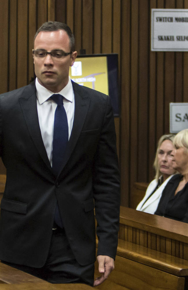 Oscar Pistorius, left, walks past June Steenkamp, back left, mother of Reeva Steenkamp, and Jenny Strydom, as he arrives in court Monday, March 17, 2014 in Pretoria, South Africa. Pistorius is on trial for the murder of his girlfriend Reeva on Valentines Day 2013. (AP Photo/Daniel Born, Pool)