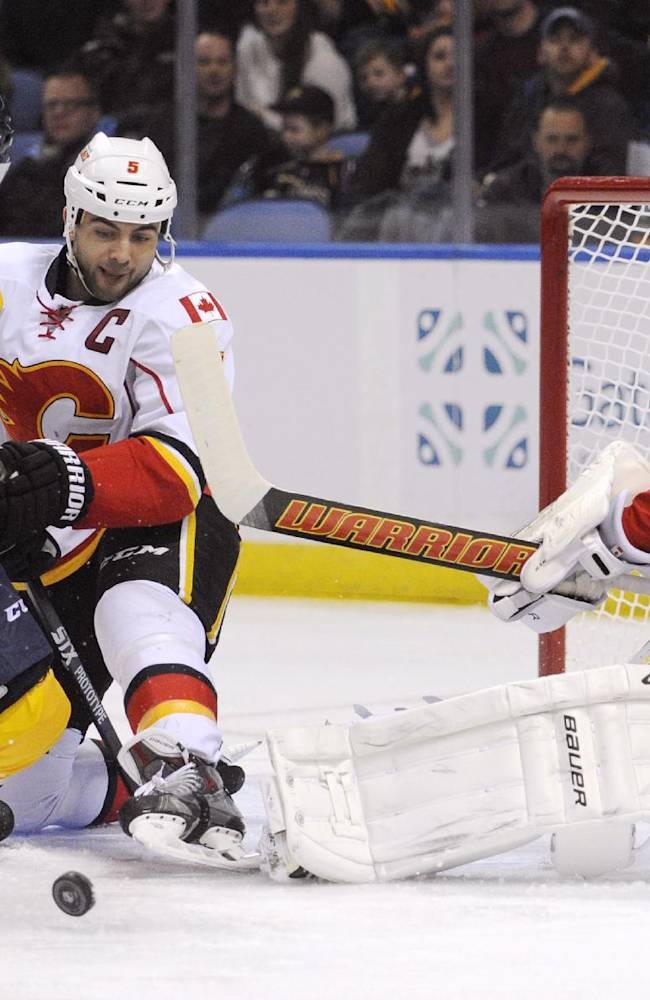 Buffalo Sabres left wing Matt Moulson (26) and Calgary Flames defenseman Mark Giordano (5) battle for the puck after a pad save by goaltender Karri Ramo (31), of Finland, during the first period of an NHL hockey game in Buffalo, N.Y., Saturday Dec. 14, 2013. Calgary won 2-1