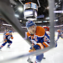 Edmonton Oilers' Andrew Ference is checked into the corner by Carolina Hurricanes' Alexander Semin during the first period of an NHL hockey game Friday, Oct. 24, 2014, in Edmonton, Alberta The Associated Press