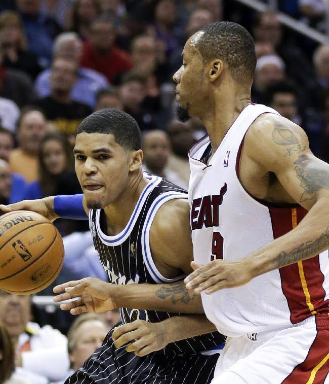 Orlando Magic's Tobias Harris, left, looks for a way around Miami Heat's Rashard Lewis, right, during the second half of an NBA basketball game in Orlando, Fla., Saturday, Jan. 4, 2014. Miami won the game 110-94