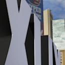 A fan takes a photo of Roman numerals erected in downtown Phoenix for Super Bowl XLIX Tuesday, Jan. 27, 2015. The New England Patriots face the Seattle Seahawks in Super Bowl XLIX on Sunday in Glendale, Ariz The Associated Press