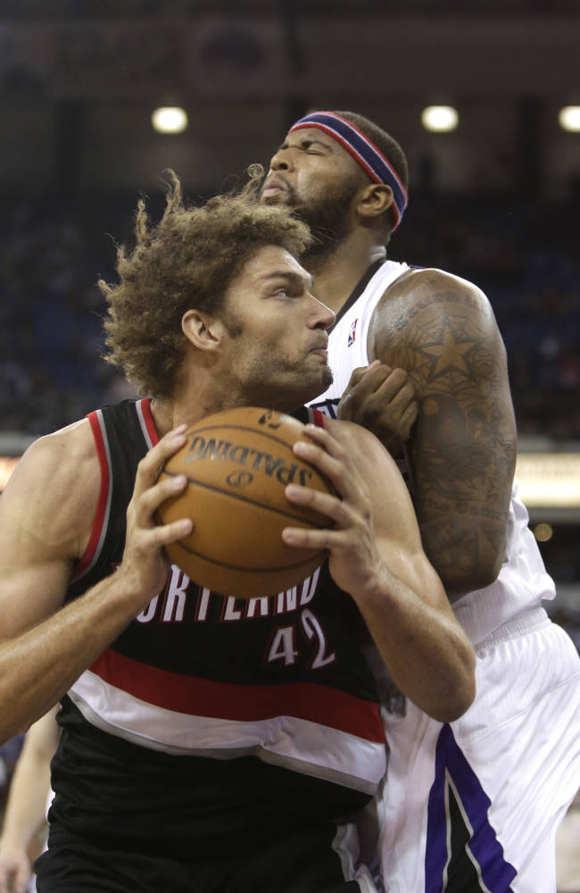 Portland Trail Blazers center Robin Lopez, left, crashes into Sacramento Kings center DeMarcus Cousins during the fourth quarter of an NBA basketball game in Sacramento, Calif., Saturday, Nov. 9, 2013.  The Trail Blazers won 96-85