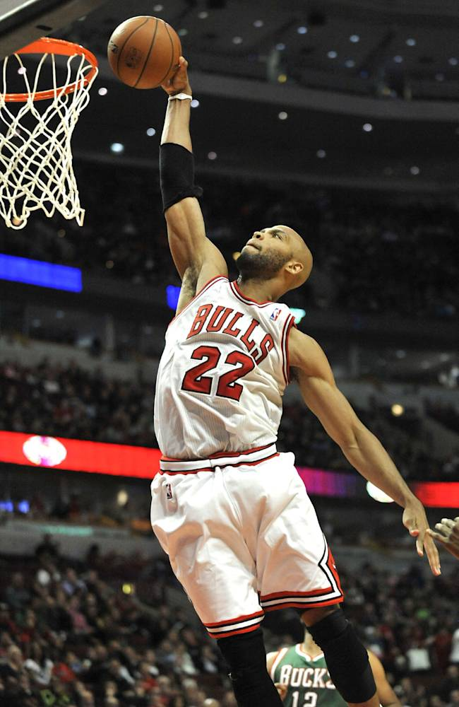 Chicago Bulls' Taj Gibson (22), dunks during the second half of an NBA preseason basketball game against the Milwaukee Bucks in Chicago, Monday, Oct. 21, 2013. Chicago won 105-84
