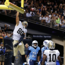 New Orleans Saints tight end Jimmy Graham (80) slam dunks over the goal post after scoring on a touchdown reception in the first half of a NFL preseason football game against the Tennessee Titans in New Orleans, Friday, Aug. 15, 2014 The Associated Press