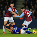 Leicester City's Leonardo Ulloa, below, is sent crashing to the floor inside the box after a tackle from Aston Villa's Ashley Westwood, left, and Ciaran Clark during their English Premier League soccer match at the King Power Stadium, Leicester, England,