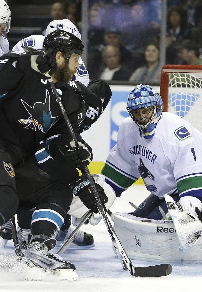 Vancouver Canucks goalie Roberto Luongo, right, defends against San Jose Sharks' Joe Thornton during the first period of an NHL hockey game on Thursday, Nov. 7, 2013, in San Jose, Calif