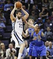 Memphis Grizzlies center Marc Gasol (33), of Spain, goes to the basket against Dallas Mavericks guard Monta Ellis (11) and forward Dirk Nowitzki, of Germany, during the first half of an NBA basketball game Wednesday, April 16, 2014, in Memphis, Tenn. (AP Photo/Lance Murphey)