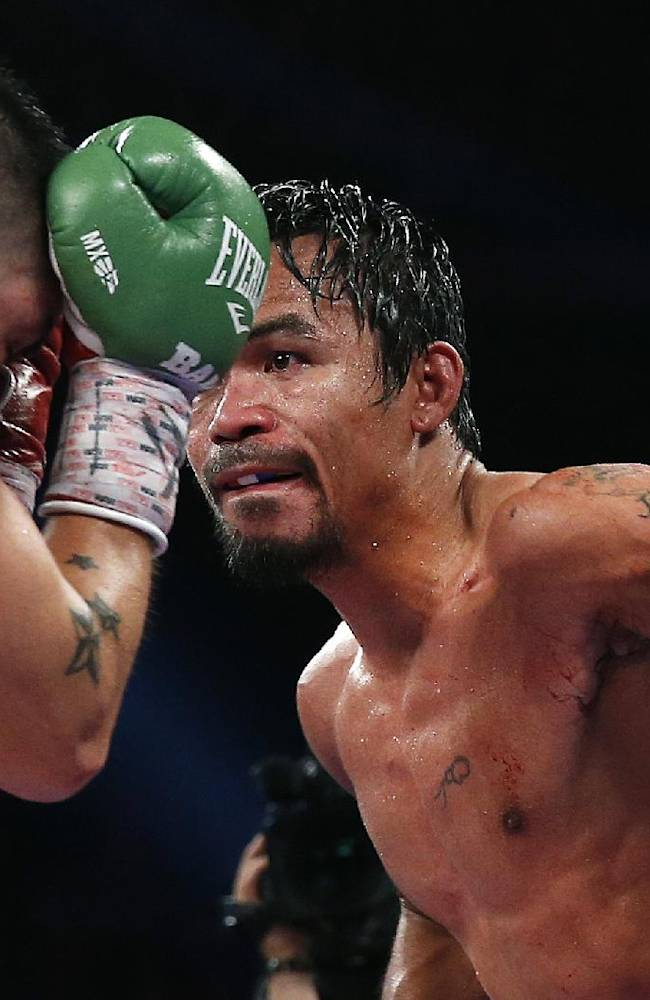 Manny Pacquiao, from the Philippines, right, lands a left to the head of Brandon Rios of the United States during their WBO world welterweight title fight Sunday, Nov. 24, 2013, in Macau. Pacquiao defeated Rios by unanimous decision on Sunday to take the title and return to his accustomed winning ways after successive defeats