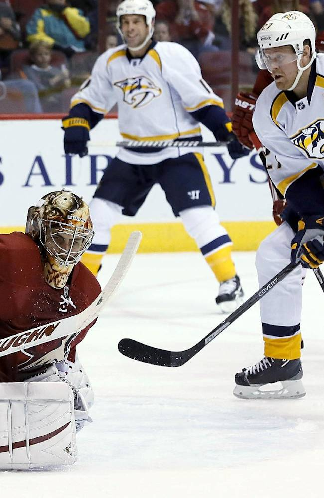 Phoenix Coyotes' Thomas Greiss (1), of Germany, makes a save on a shot by Nashville Predators' Patric Hornqvist (27), of Sweden, as Predators' David Legwand watches during the first period of an NHL hockey game Thursday, Oct. 31, 2013, in Glendale, Ariz