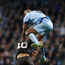 Manchester City's Vincent Kompany, right, jumps over Roma's Francesco Totti during a Champions League group E soccer match between Manchester City and Roma at the Etihad Stadium, Manchester, England, Tuesday, Sept. 30, 2014