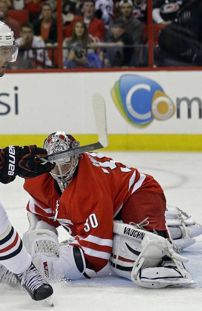 Chicago Blackhawks' Patrick Sharp (10) scores on Carolina Hurricanes goalie Cam Ward during the first period of an NHL hockey game in Raleigh, N.C., Tuesday, Oct. 15, 2013