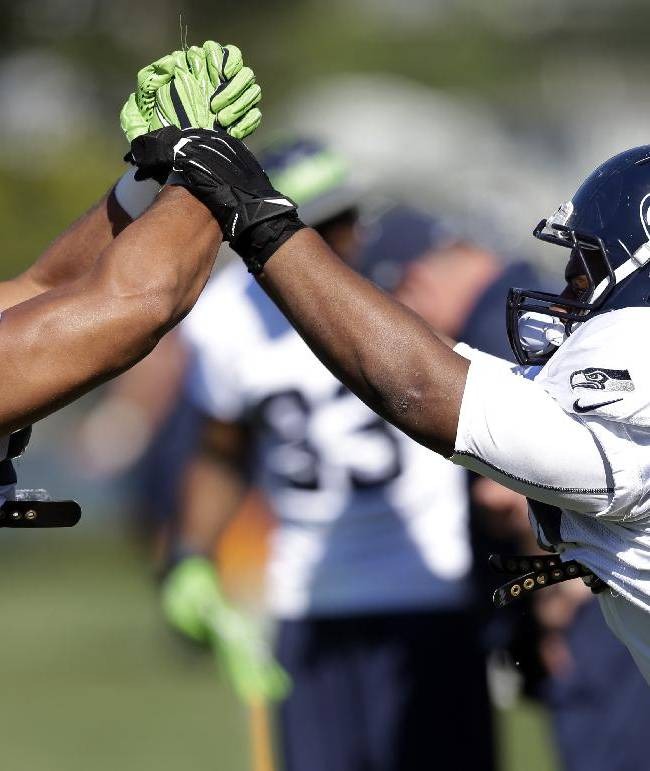 Seattle Seahawks' Jordan Hill, left, and D'Anthony Smith work through a drill at an NFL football camp practice Tuesday, July 29, 2014, in Renton, Wash