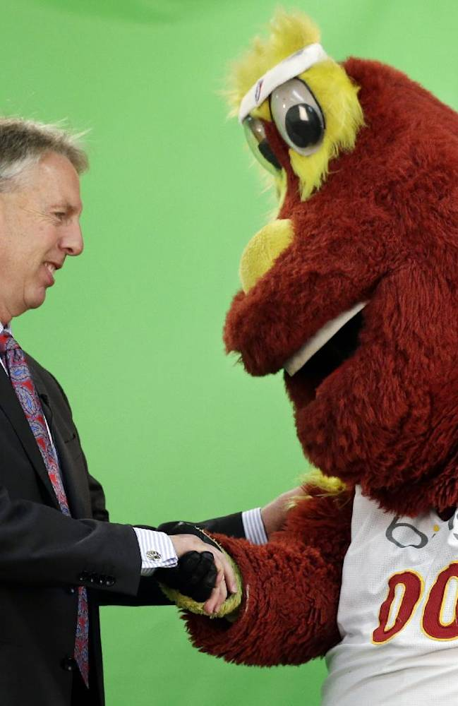 Seattle Storm head coach Brian Agler, left, shakes hands with team mascot Doppler at the team's annual media day Wednesday, May 7, 2014, in Seattle. The team opens against the Los Angeles Sparks on May 16 in Seattle