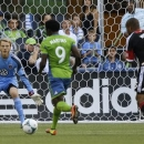 Seattle Sounders' Obafemi Martins (9) faces off with D.C. United goalkeeper Joe Willis, left, as United's Ethan White runs in to defend at right, just before Martins scored a goal in the first half of an MLS soccer match, Wednesday, July 3, 2013, in Seattle. (AP Photo/Ted S. Warren)