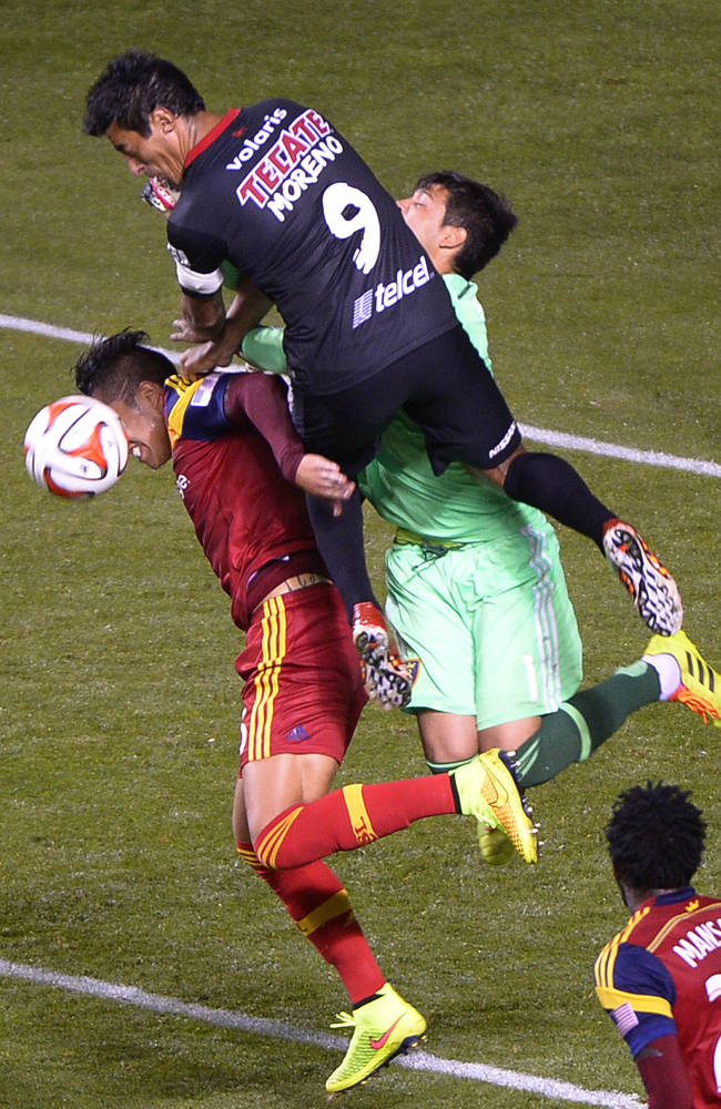 Club Tijuana's Alfredo Moreno collides with Real Salt Lake defender Carlos Salcedo (16) and goalkeeper Lalo Fernandez. Mexican team Club Tijuana tied 1-1 with Real Salt Lake, Tuesday, Aug. 12, 2014, at Rio Tinto Stadium in Sandy, Utah