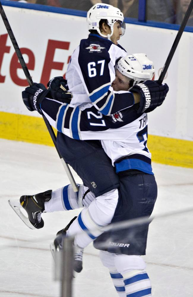 Winnipeg Jets' Michael Frolik (67) and Eric Tangradi (27) celebrate a goal against the Edmonton Oilers during third period NHL hockey action Tuesday, Oct. 1, 2013, in Edmonton, Alberta