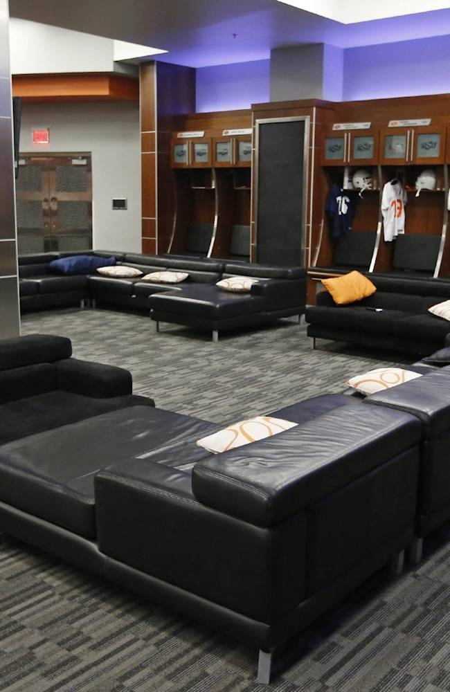 This Sept. 5, 2013 photo shows the Oklahoma State University football locker room in Stillwater, Okla. With weight rooms as big as football fields, more flat screen TVs than a Best Buy and enough leather furniture to fill Trump Plaza, players have no reason to go back to the dorms