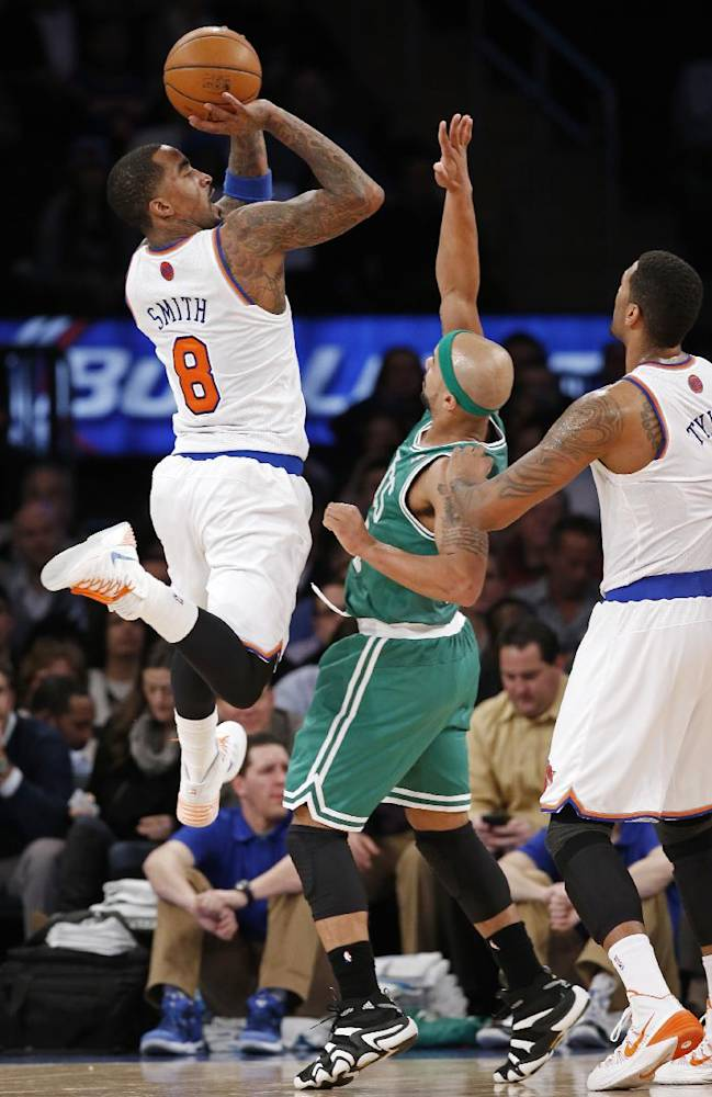 New York Knicks guard J.R. Smith (8) shoots over the defense of Boston Celtics guard Jerryd Bayless (11) as Knicks forward Jeremy Tyler (4) watches from the floor in the second half of an NBA basketball game at Madison Square Garden in New York, Tuesday, Jan. 28, 2014. The Knicks defeated the Celtics 114-88