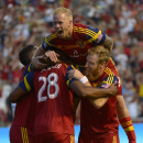 Real Salt Lake midfielder Luke Mulholland, top, forward Olmes Garcia, left, and defender Nat Borchers (6) mob defender Chris Schuler (28) after one of his two goals during the first half against D.C. United in an MLS soccer game Saturday, Aug. 9, 2014, in