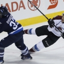 Winnipeg Jets' Dustin Byfuglien (33) takes out Colorado Avalanche's Colorado Avalanche's Zach Redmond (22) during first-period NHL hockey game action in Winnipeg, Manitoba, Friday, Dec. 5, 2014 The Associated Press