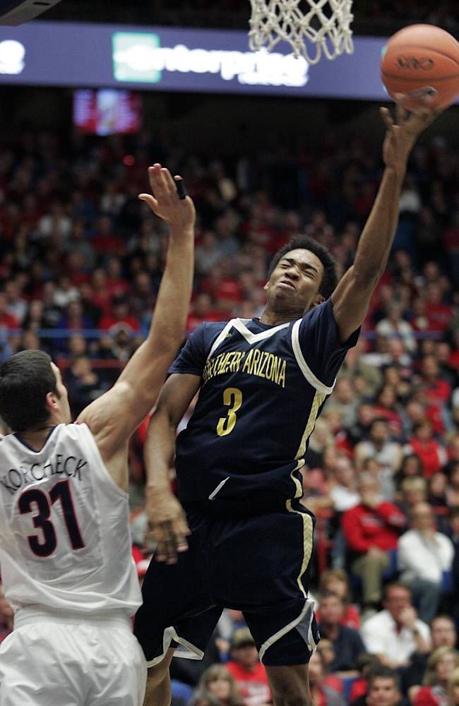 Northern Arizona's Christopher Miller (3) shoots for two against Arizona's Matt Korcheck (31) in the second half of an NCAA college basketball game on Monday, Dec. 23, 2013 in Tucson, Ariz. Arizona won 77 - 44