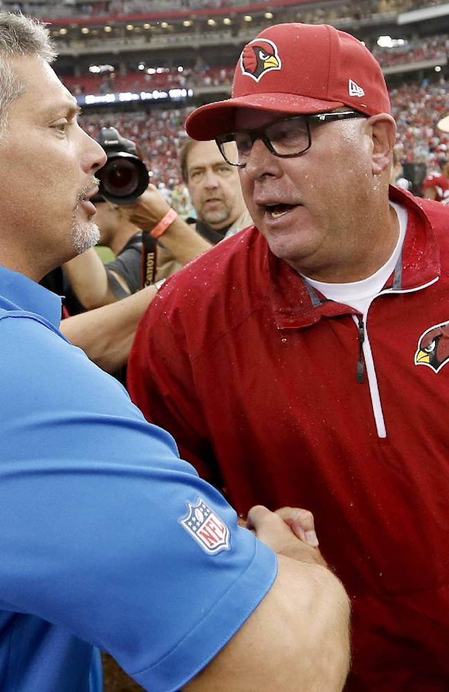 As he carries the game ball, Arizona Cardinals head coach Bruce Arians, right, shakes hands with Detroit Lions head coach Jim Schwartz after an NFL football game on Sunday, Sept. 15, 2013, in Glendale, Ariz.  The Cardinals defeated the Lions 25-21
