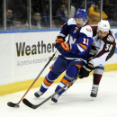 New York Islanders' Lubomir Visnovsky (11) and Colorado Avalanche's Patrick Bordeleau (58) battle for the puck around the boards in the first period of an NHL hockey game on Saturday, Feb. 8, 2014, in Uniondale, N.Y The Associated Press
