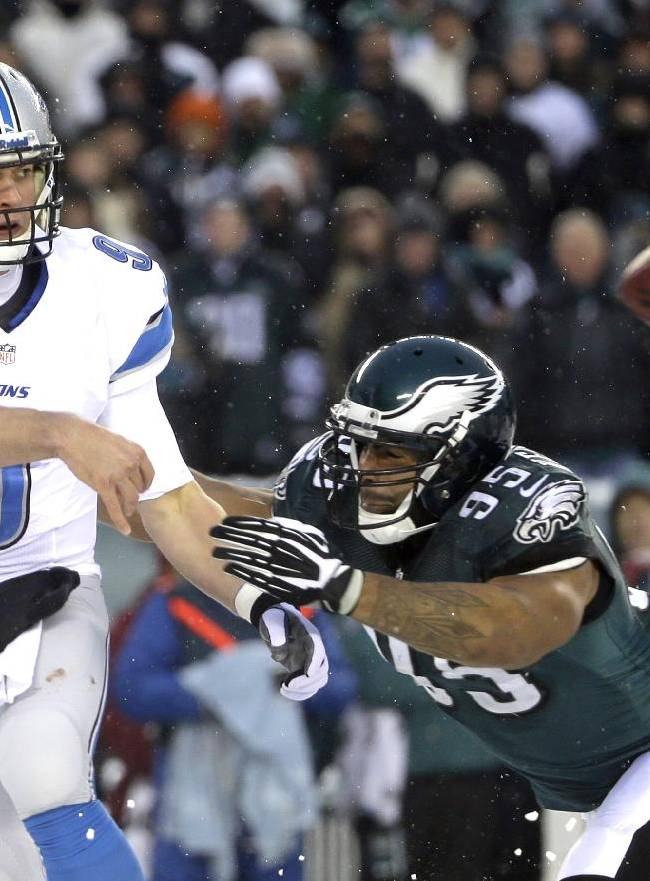 Detroit Lions' Matthew Stafford, left, passes under pressure from Philadelphia Eagles' Mychal Kendricks during the second half of an NFL football game on Sunday, Dec. 8, 2013, in Philadelphia