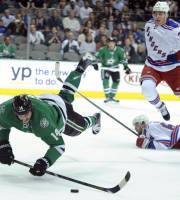 Dallas Stars left wing Jamie Benn (14) can't stay on his skates after leaping over New York Rangers defenseman Anton Stralman (6) during the first period of an NHL hockey game, Thursday Nov. 21, 2013 in Dallas. (AP Photo/Matt Strasen)