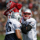 New England Patriots tight end Rob Gronkowski, right, runs a drill with running back James Develin during NFL football training camp in Foxborough, Mass., Saturday, July 26, 2014. (AP Photo) The Associated Press