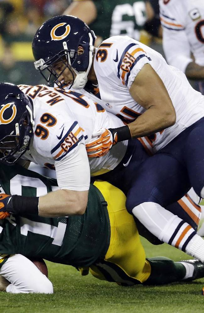 Green Bay Packers quarterback Aaron Rodgers is sacked by Chicago Bears' Shea McClellin (99) and Isaiah Frey (31) during the first half of an NFL football game Monday, Nov. 4, 2013, in Green Bay, Wis