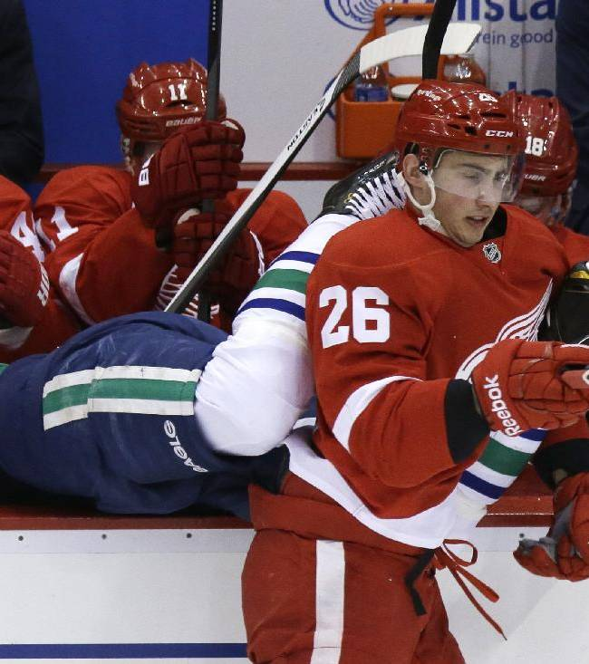 Detroit Red Wings right wing Tomas Jurco (26) checks Vancouver Canucks defenseman Alexander Edler of Sweden into the Red Wings bench during the first period of an NHL hockey game in Detroit, Monday, Feb. 3, 2014