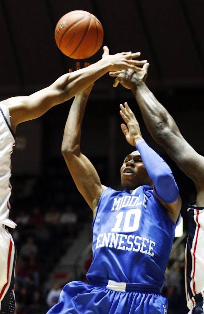 Mississippi forward Sebastian Saiz (11) and center Demarco Cox (4) block a shot by Middle Tennessee State guard Jaqawn Raymond (10) in the second half of an NCAA college basketball game in Oxford, Miss., Saturday, Dec. 14, 2013. Mississippi won 72-63