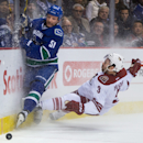 Vancouver Canucks' Derek Dorsett, left, and Arizona Coyotes' Keith Yandle crash into the boards while chasing after the puck during the first period of an NHL hockey game in Vancouver, British Columbia, on Friday Nov. 14, 2014 The Associated Press
