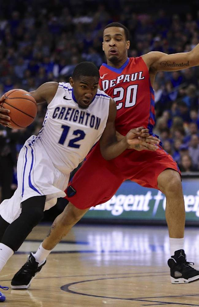 Creighton's Jahenns Manigat (12) drives past DePaul's Brandon Young (20) in the first half of an NCAA college basketball game in Omaha, Neb., Friday, Feb. 7, 2014