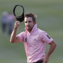 Jbe Kruger of South Africa, wearing black ribbons as a sign of his respect to the former South African President Nelson Mandela, reacts after finishing the 18th hole during the day two match of the 2013 Hong Kong Open golf tournament in Hong Kong, Friday, Dec. 6, 2013. (AP Photo/Kin Cheung)