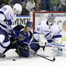 St. Louis Blues' Jaden Schwartz (9) goes to his knees as he tries to squeeze the puck between Tampa Bay Lightning's Ondrej Palat (18) and goalie Ben Bishop (30) during the second period of an NHL hockey game, Tuesday, March 4, 2014 in St. Louis The Associ